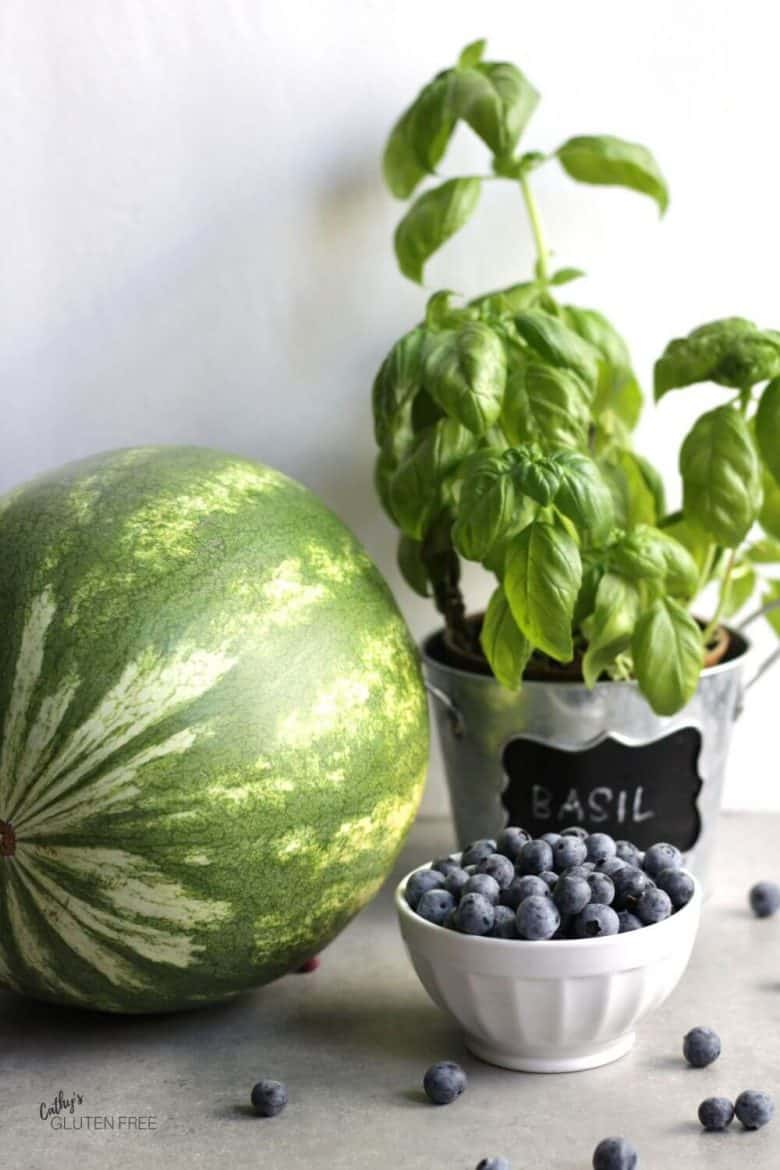 whole watermelon, basil plant, bowl of fresh blueberries