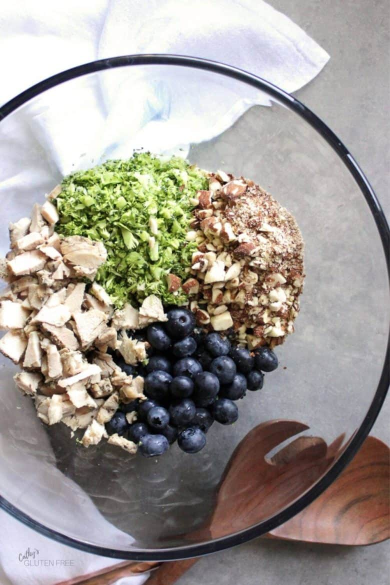 chopped broccoli, almonds, chicken, and whole blueberries in a glass bowl
