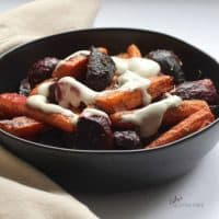 roasted beets and carrots, drizzled with yogurt, in a black bowl