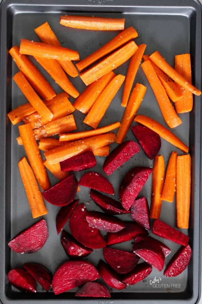 carrots and beets spread out on a baking pan ready to be roasted