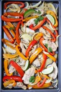 roasted red and yellow peppers, onions, and chicken strips spread out over a sheet pan, garnished with cilantro and lime wedges