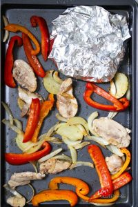 foil wrapped tortillas tucked into the corner of sheet pan with vegetables and meat