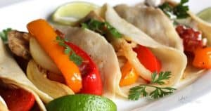 red and orange bell peppers with chicken strips in a tortilla