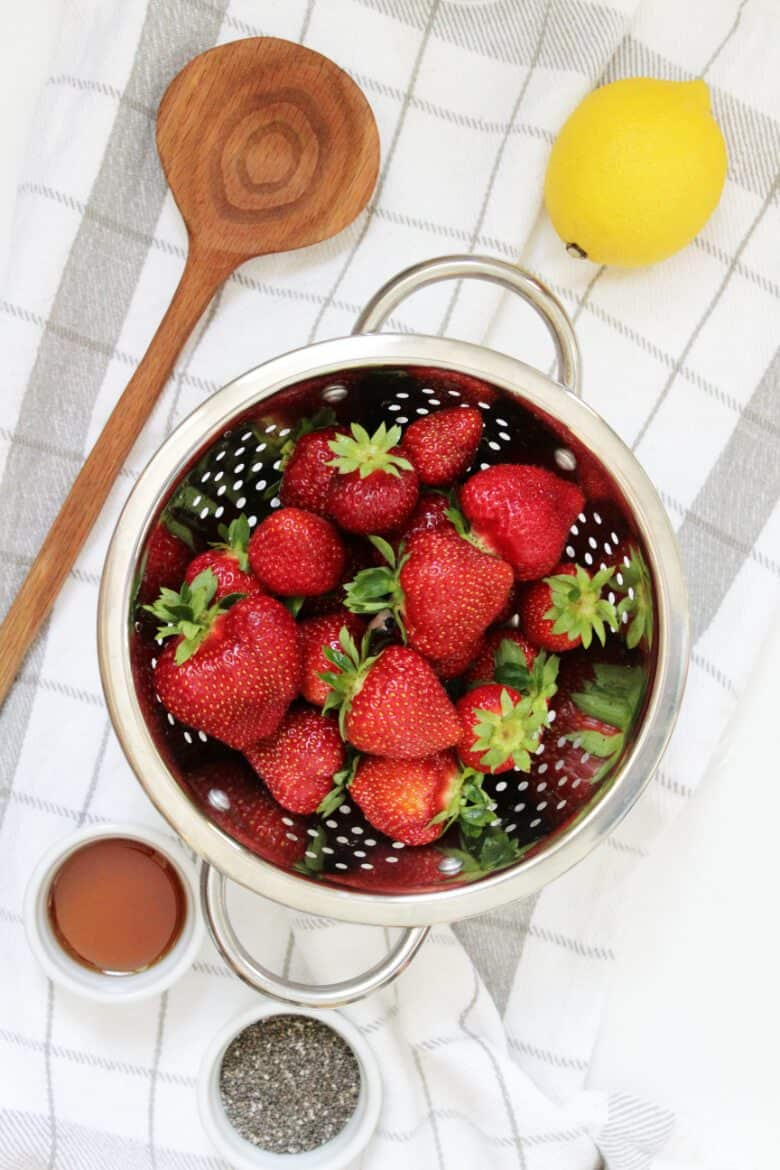strawberries in a colander with lemon and chia seeds on the side