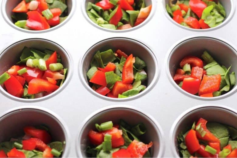 chopped red peppers, green onions, and spinach in muffin cups