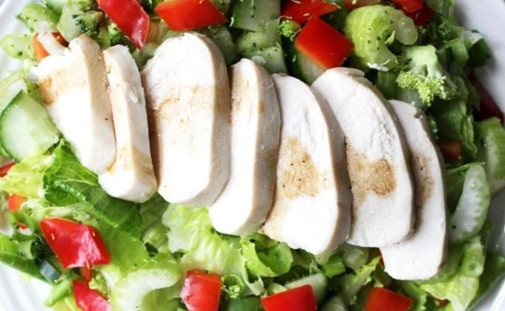 sliced cooked chicken laid across a lettuce salad