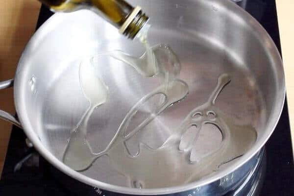 oil is drizzled into stainless steel pan