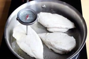 Three cooked chicken breasts in stainless steel pan with meat thermometer inserted in one