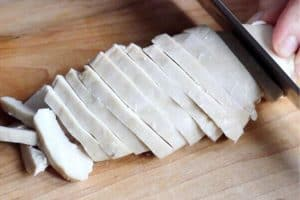 cooked chicken breast being sliced