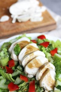 sliced, cooked chicken on salad and more on board in background