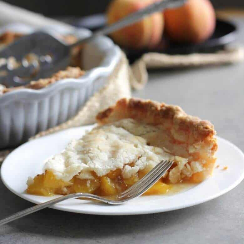 single slice of gluten free peach pie with whole pie and fresh peaches in the background