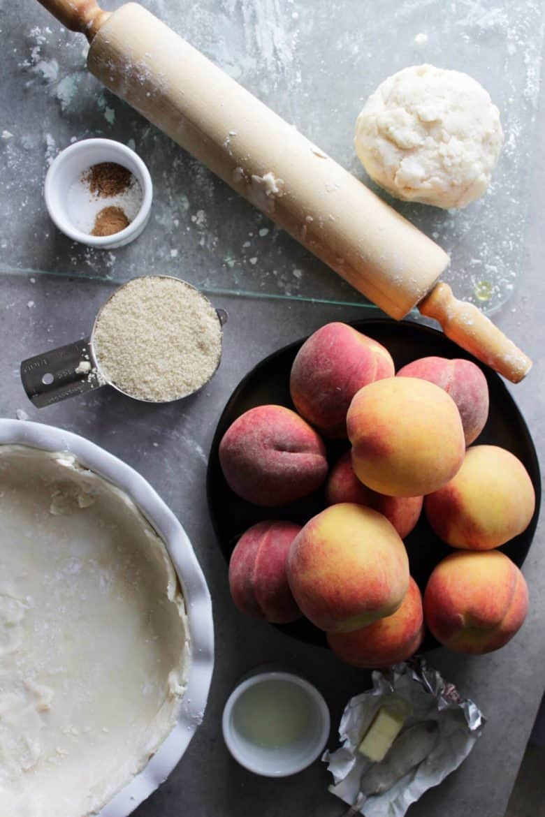 flat lay of fresh peaches, unbaked crust in pie plate, sugar, rolling pin, and other ingredients