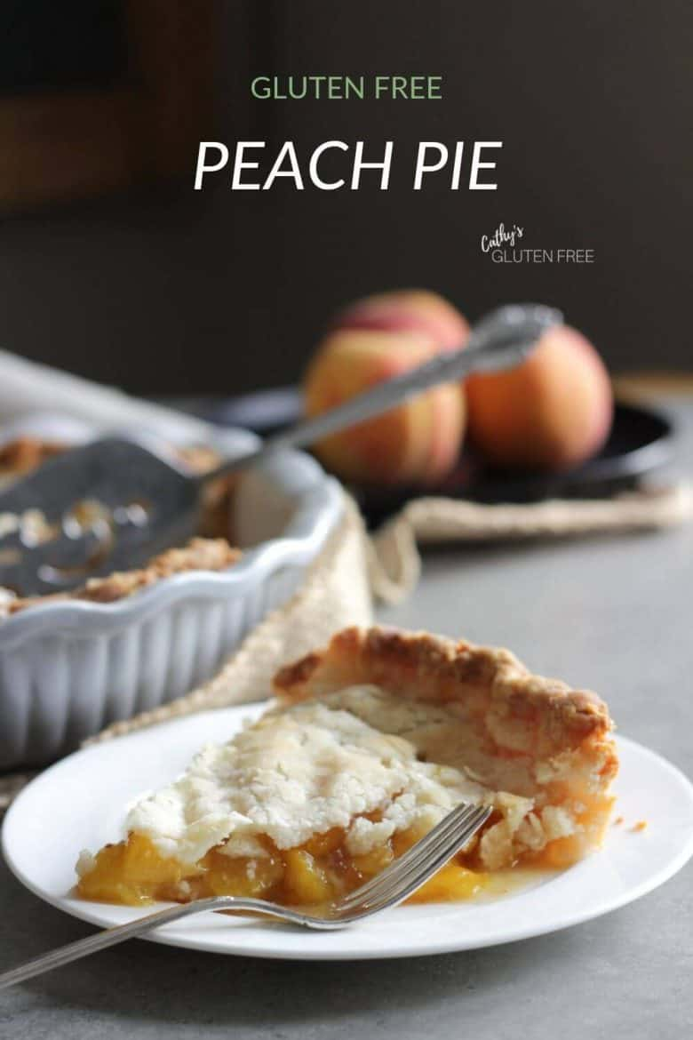 slice of peach pie on white plate with fresh peaches in background