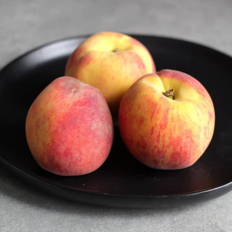 three fresh peaches on black plate