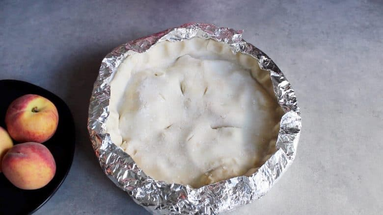 unbaked pie with foil collar covering the edges