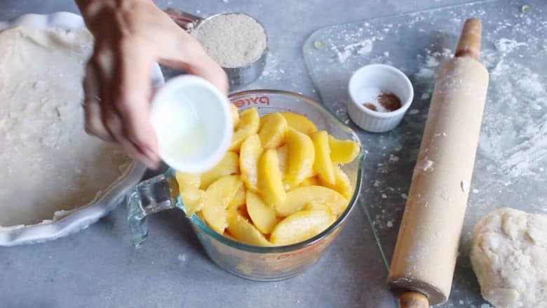 lemon juice is poured onto fresh peach slices