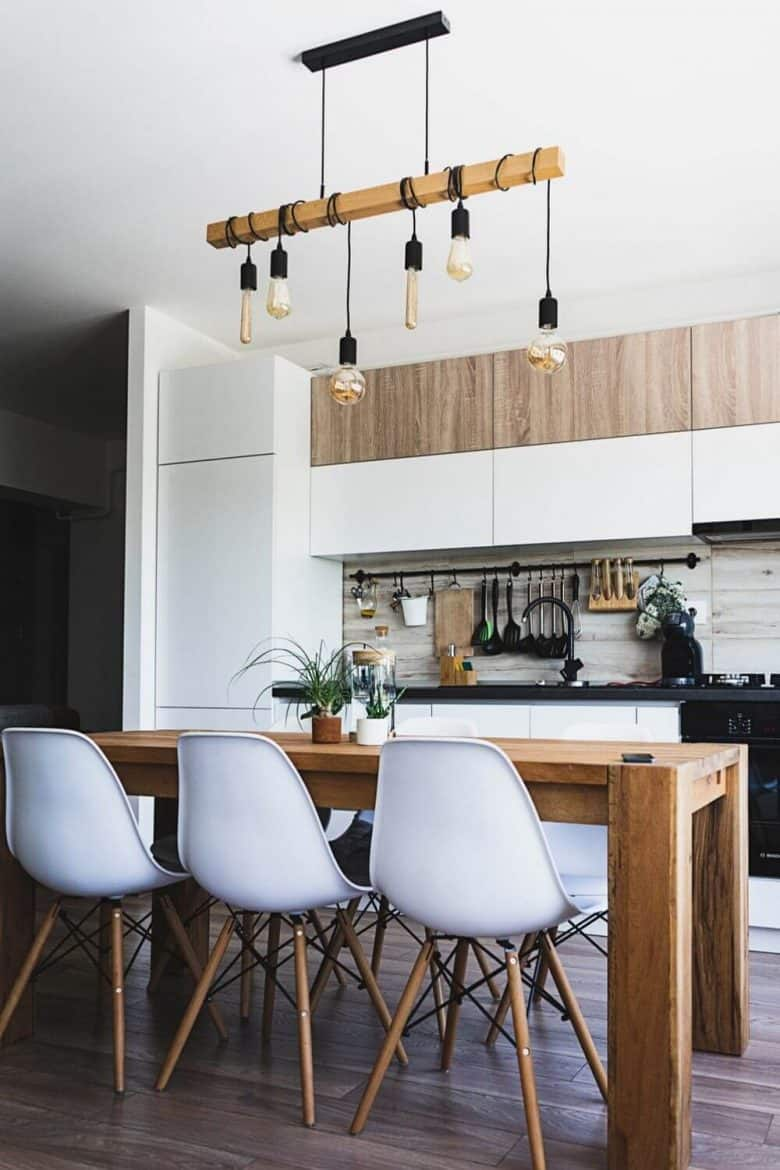 white kitchen with wood trim, white chairs at wooden island