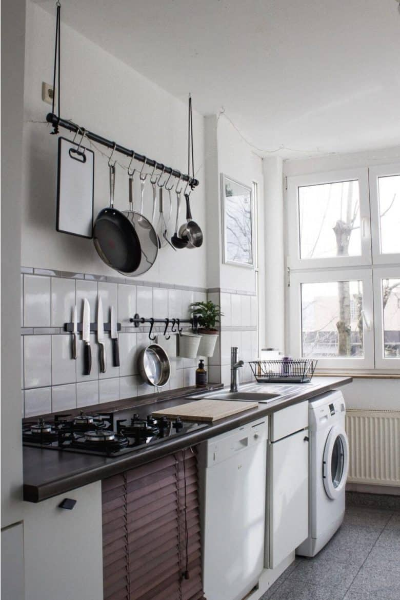 kitchen utensils hanging on wall above counter