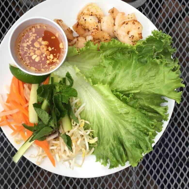 lettuce, shrimp, sprouts, carrot slivers, and sauce on white plate of Khon, one of the restaurants in Pensacola Florida
