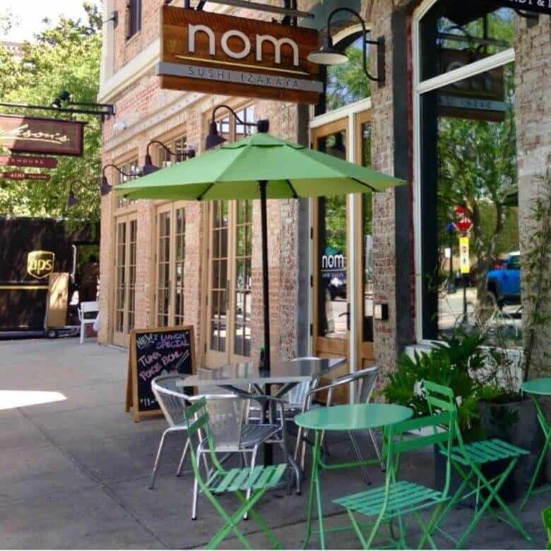lime green umbrella and green cafe table and chairs in front of Nom, one of the restaurants in Pensacola Florida