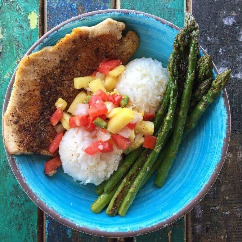 fish, rice, and asparagus with pineapple salsa on blue plate
