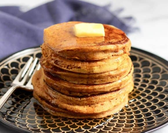 stack of pancakes with pat of butter on top and maple syrup drizzled all over