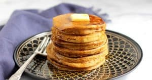 gluten free pumpkin pancakes stacked with pat of butter on top
