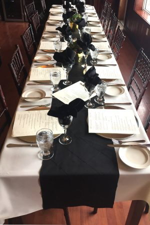 long table with white tablecloth and black runner, set for dinner