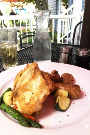 chicken and vegetables on pink plate on outdoor patio