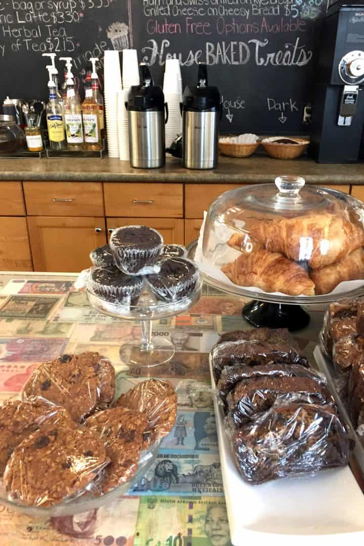 plastic-wrapped muffins and loaf on coffee shop counter