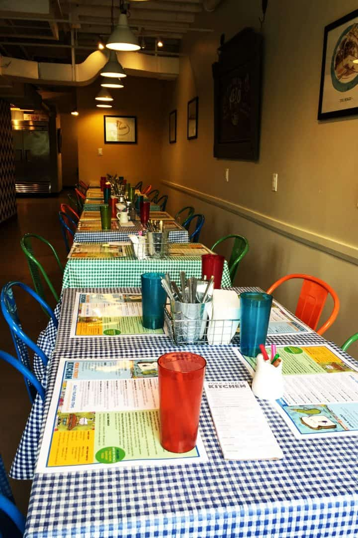 long row of tables with colourful chairs and tumblers