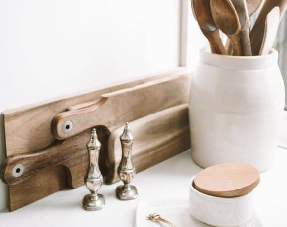 white crock with wooden utensils and wooden cutting boards on white counter