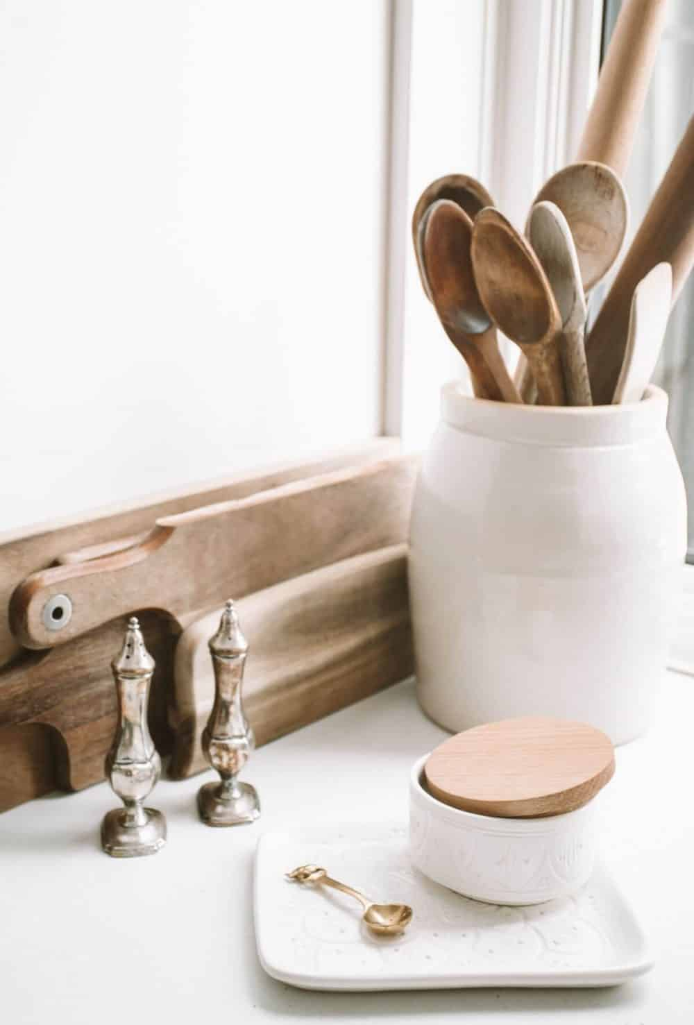 wooden kitchen tools in white crock on white counter