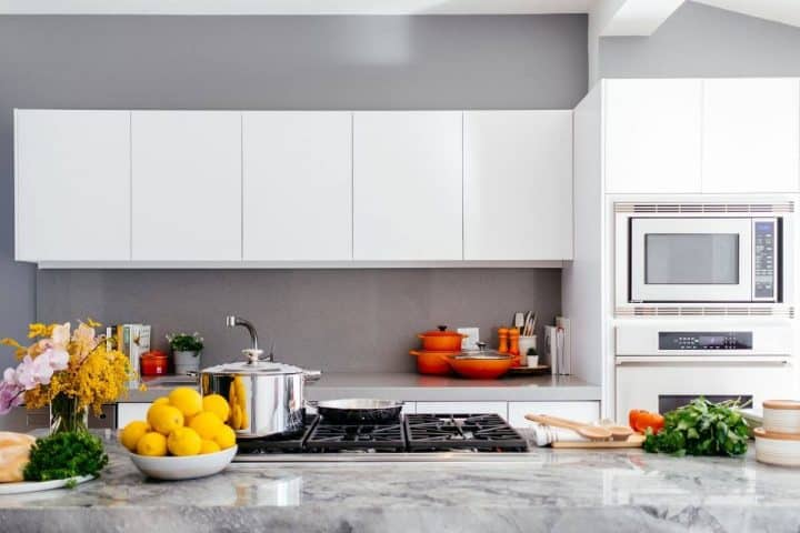 white kitchen cupboards, marble countertop with accessories