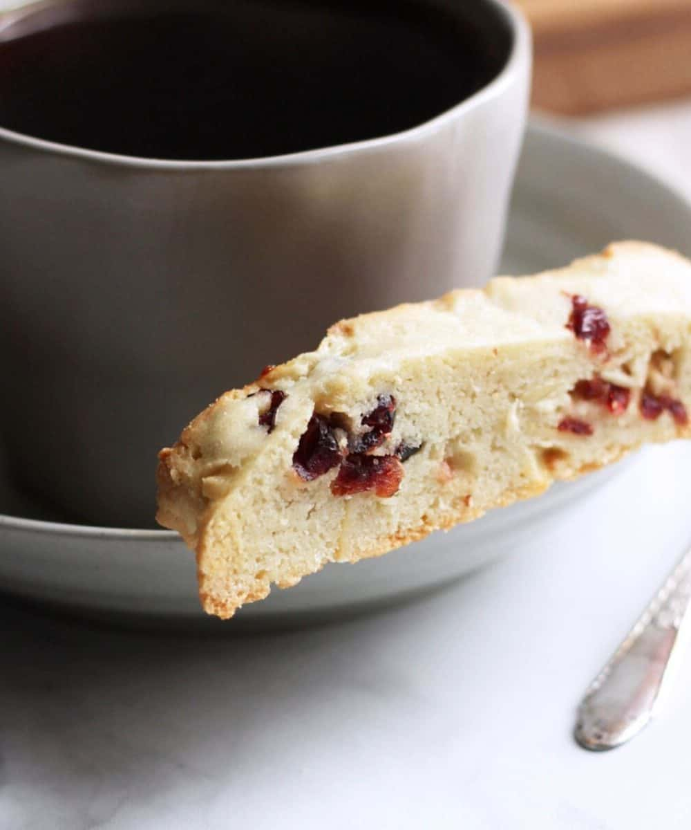 cranberry almond biscotti resting on a saucer by cup of coffee