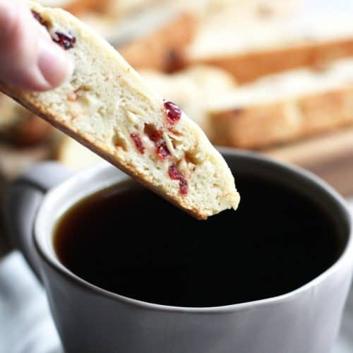cranberry-almond biscotti dipping into coffee
