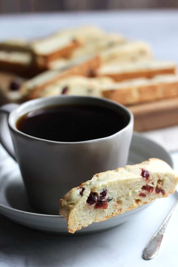 cranberry almond biscotti with coffee and more biscotti scattered in background