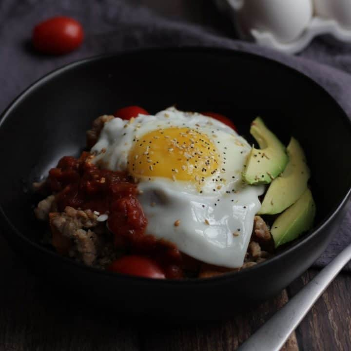 soft egg on top of dark bowl of food with sliced avocado on the side
