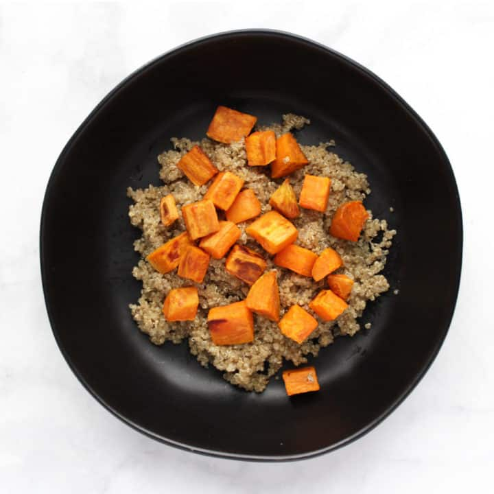 sweet potatoes chunks on quinoa in black bowl