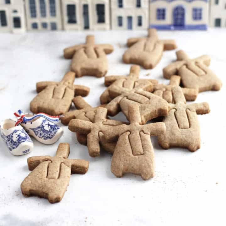 windmill-shaped cookies scattered on white surface with ceramic blue and white houses in background