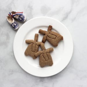 """3 windmill cookies on white plate, ceramic """"wooden"""" shoes to side"""