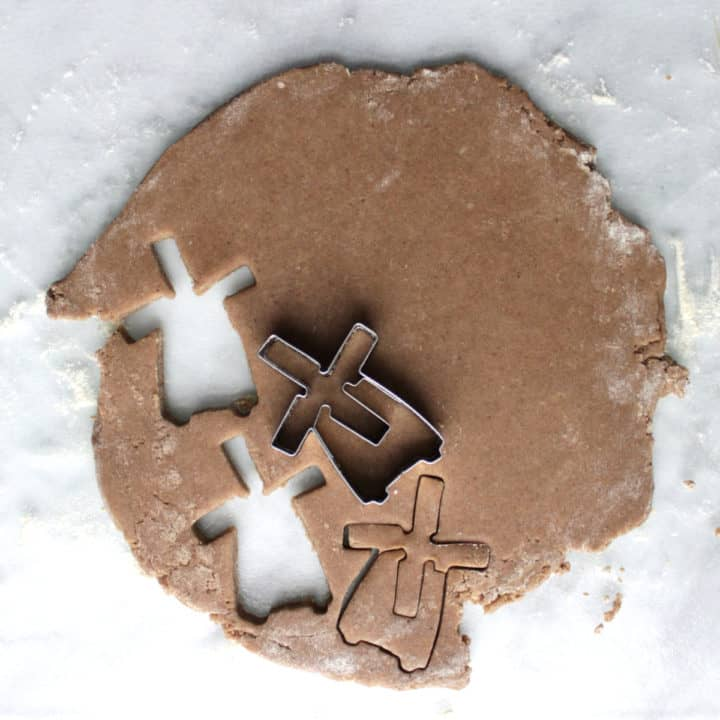top down view of cookie cutter cutting out a few windmill-shaped cookies
