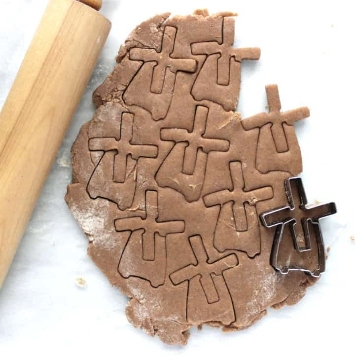top down view of windmill-shaped cookies cut into rolled dough with rolling pin to side