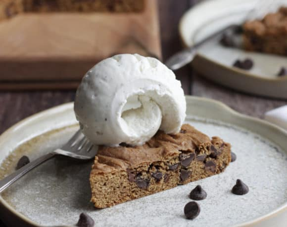 wedge of chocolate chip cookie cake with a scoop of vanilla ice cream on top