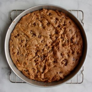 baked chocolate chip cookie cake in round pan