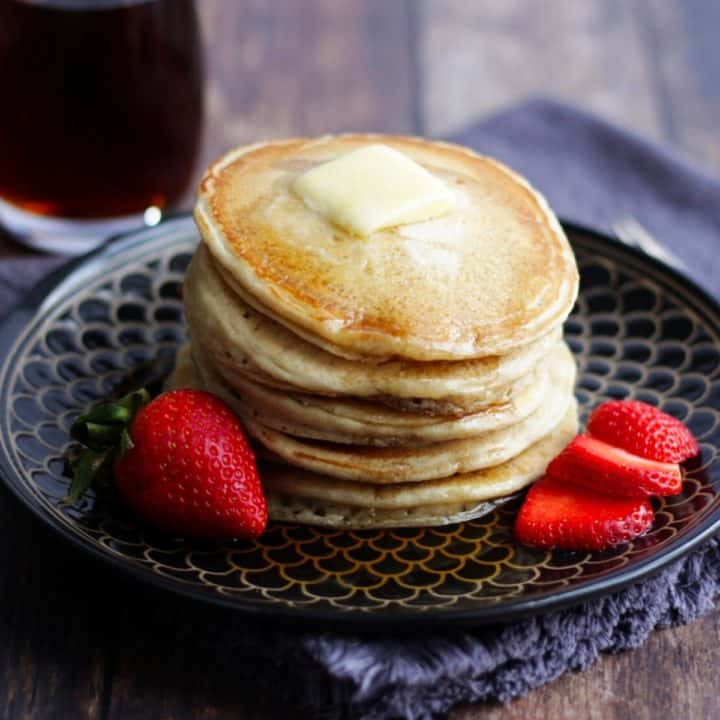 stack of gluten free pancakes with butter on top, garnished with strawberries