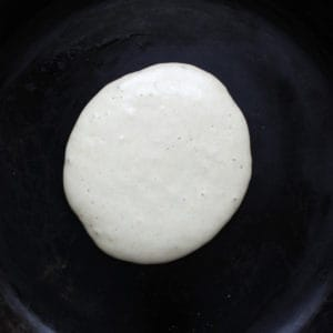 pancake cooking in pan with small bubbles on top