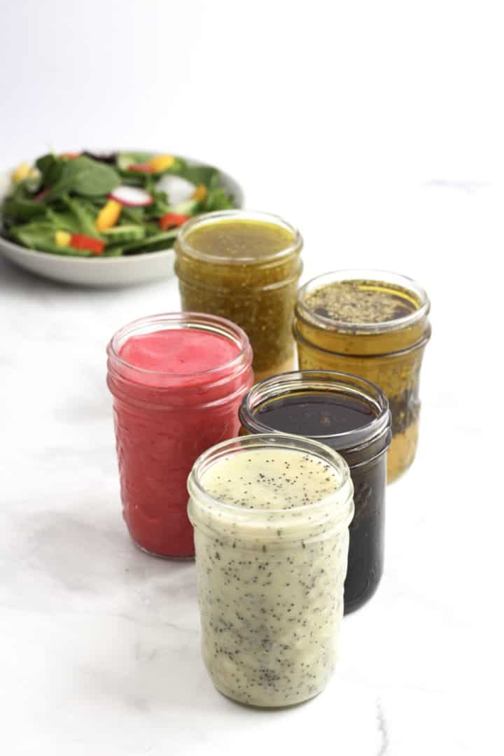 5 jars of low carb salad dressing with lettuce salad in background