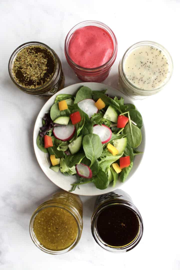 top down view of salad dressings surrounding a bowl of salad