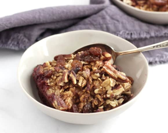 bowl of baked oatmeal with raisins and pecans on top